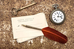 Old post cards, clock, key and feather pen Stock Image