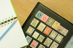 Old postage stamp. And notebook with wood background Stock Photos