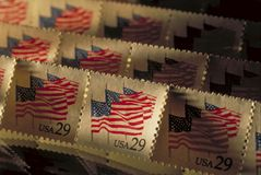 Old postage stamps raked in sunlight. Rows of old USA postage stamps are raked by low window sunlight. A pattern of American flags is repeated on the rows of Royalty Free Stock Photography