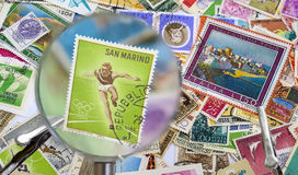Old postage stamps under magnification lens Royalty Free Stock Photography