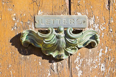 Old postal brass mailbox gainst a colored wooden door Stock Images