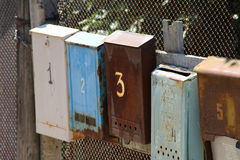 Old postbox on the fence Royalty Free Stock Photo
