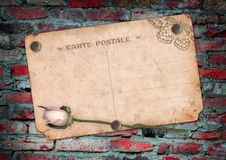 Old postcard on the brick wall Stock Photography