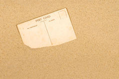 Old postcard in sand background, blank with copy space Stock Images