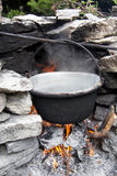 Old pot on fire outside. Old metal pot on the fire between stones outside Royalty Free Stock Photo