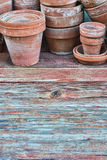 Old pots on barnwood. Old clay flower pots on a rough wooden table with faded paint stock image