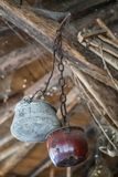 Old pots hanging from the ceiling. Old pots covered in spider web hanging from the ceiling in an old farm building Stock Image