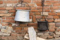 Old pots and pans hanging on wall Royalty Free Stock Images