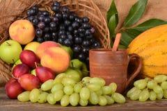 Old potters clay mug and colorful fruits, still life Royalty Free Stock Photos