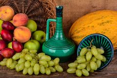 Old potters jug and colorful fruits, still life Stock Image