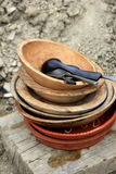 Old pottery plates and wooden bowls on table Royalty Free Stock Photos