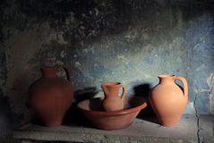 Old Pottery. Still live with ancient pottery items in a stone counter and lit by a window Stock Photography