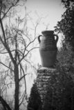 Old pottery urn outdoors. Black and white close up of old pottery urn on stone structure outdoors Stock Photography