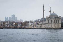Old Power Meets New Power In Form Of Mosque And Skyscrapers. View From The River On Cloudy And Foggy Day. Royalty Free Stock Images