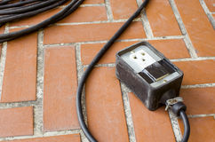 Old power outlet on brown floor tile Stock Photo