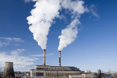 Old power plant producing white smoke Stock Images