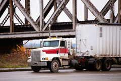 Old powerful bonneted truck with bulk trailer under bridge Stock Photos