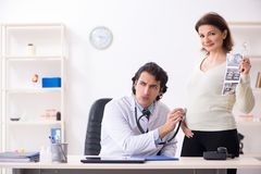 The old pregnant woman visiting young male doctor. Old pregnant woman visiting young male doctor stock photography