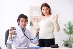 The old pregnant woman visiting young male doctor. Old pregnant women visiting young male doctor stock photos