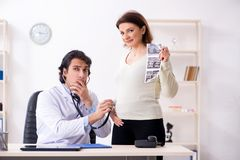The old pregnant woman visiting young male doctor. Old pregnant women visiting young male doctor royalty free stock photo