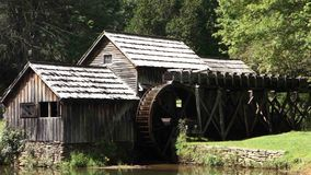 An old, preserved water wheel turning slowly at historic mabry mill. Power being generated by water the old-fashioned way at a grist mill in virginia stock video footage