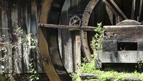 An old, preserved water wheel turning slowly. Power being generated by water at a grist mill in virginia stock video