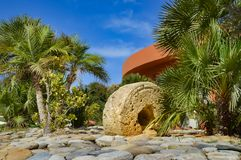 Old press wheel serving as a garnish in a pebble. And palm grove in Maleme in western Crete Stock Photography
