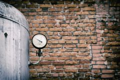 Old pressure gauge of the tank against the backdrop of a brick wall. Pressure sensor. Copy space Royalty Free Stock Image