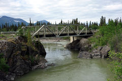 An old, pretty bridge in canada. A lovely bridge over a fast-moving river in the yukon territories stock images