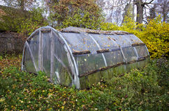 Old primitive plastic greenhouse in autumn farm garden Stock Image