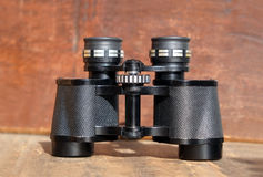 OLd prism black color binoculars over wooden background closeup. Old prism black color binoculars on vintage wooden background front view closeup stock photography