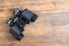 Old prism black color binoculars over wooden background closeup. Old prism black color binoculars on vintage wooden background top view closeup stock photos