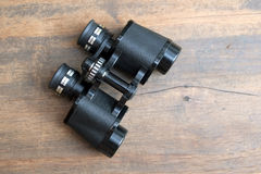 Old prism black color binoculars over wooden background closeup. Old prism black color binoculars on vintage wooden background top view closeup stock images