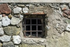 Old prison cell small window with metal bars and rock brick wall. Retro and vintage concept image stock images