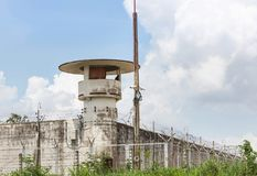 Old prison guard tower or watchtower with security systems barbed wire fence. Around the wall Stock Image