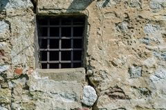 Old prison window in castle cell wall with metal bars. Dark age. Retro and vintage concept image Stock Photos