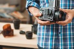 Old professional film photo camera close-up. Old professional medium format photo camera close-up. Unrecognizable photographer holding film camera, blurred stock photo