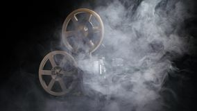 Old projector showing film in the smoke. Studio black background