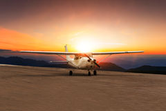 Old propeller plane taxi on airport runway against beautiful sun Royalty Free Stock Photos