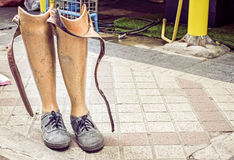 Old prosthetic legs set on a cement floor Royalty Free Stock Images