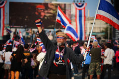 Old protester with dress decorations raises Thai flag. BANGKOK - JAN 25: Unidentified old protester with dress decorations raises Thai flag to anti government at Stock Photography