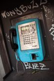 Old public blue payphone, urban mood, graffiti buzz text. Dirty buttons and screen, old technology, forgotten stock photography