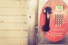Old public coin-operated telephone. Vintage tone Royalty Free Stock Photo