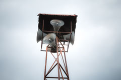 Old public loudspeakers broadcast on high tower. With long distance tower Stock Image