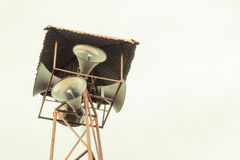 Old public loudspeakers broadcast on high tower. With long distance tower Stock Photo