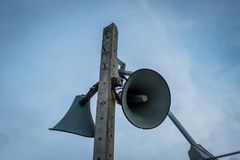 Old public loudspeakers broadcast on high tower. With long distance tower Royalty Free Stock Image