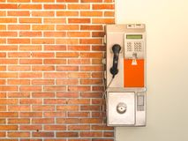 An old public payphone with red brick wall. An old public payphone with red brick wall at the university in Thailand stock images