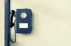 Old public payphone on the wall. Brown metal phone. Disk telephone. stock photography