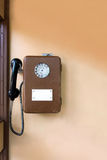 Old public payphone on the wall. Brown metal phone. Disk telephone royalty free stock images
