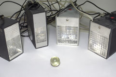 Old pulse electronic flashes, surrounding the small glass ball. Closeup Stock Photography